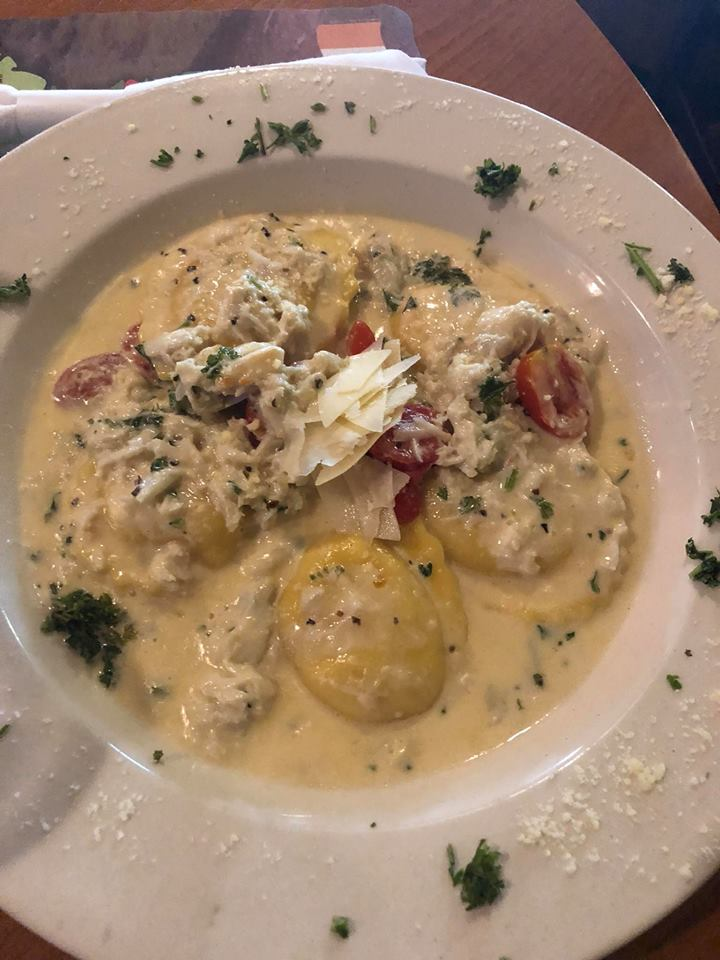 lobster ravioli in a crab cream sauce served in a shallow bowl