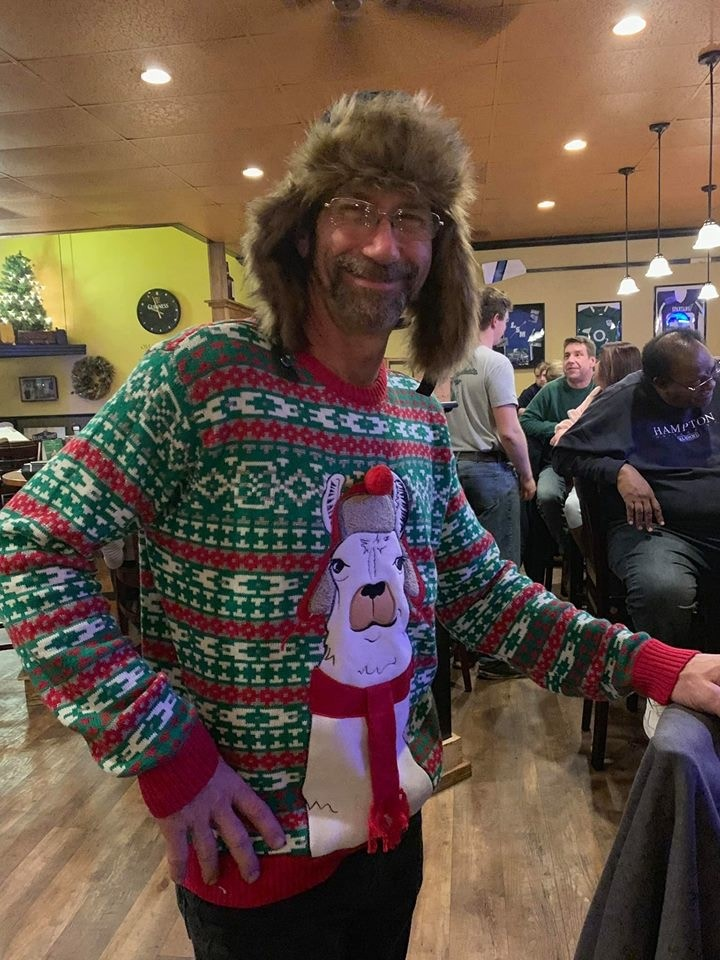 man wearing christmas sweater with a llama wearing a hat on it