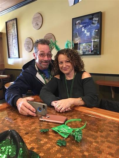 couple sitting at a bar decorated for st patricks day