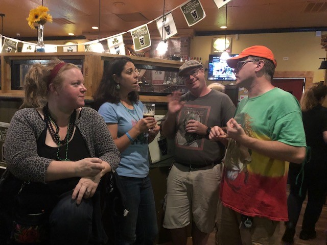 friends standing with drinks in a bar
