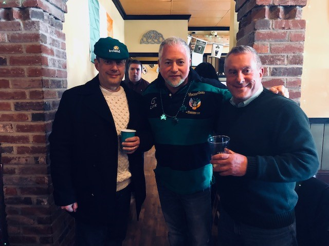 three men standing in a  bar with drinks