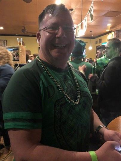 man wearing green shirt and green and gold beads