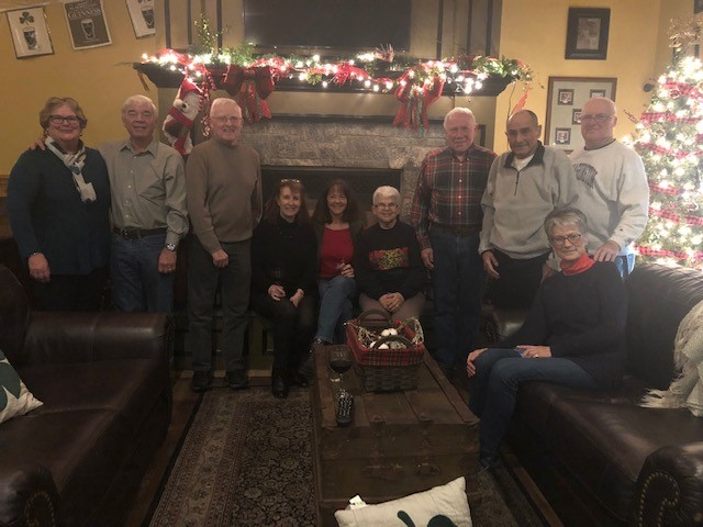 family in front of fire place decorated for christmas