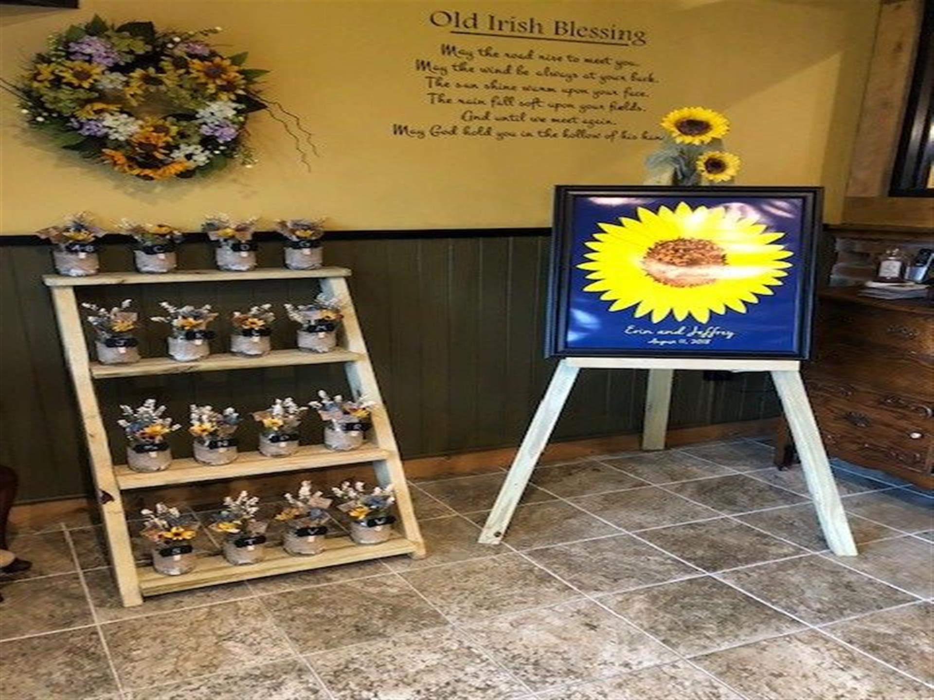 tiered stand with favors on it and a sunflower painting on an easel