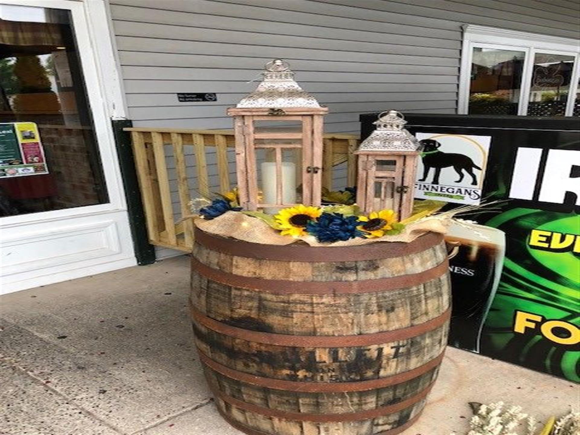wine barrel topped with two lanterns and sunflower decorations