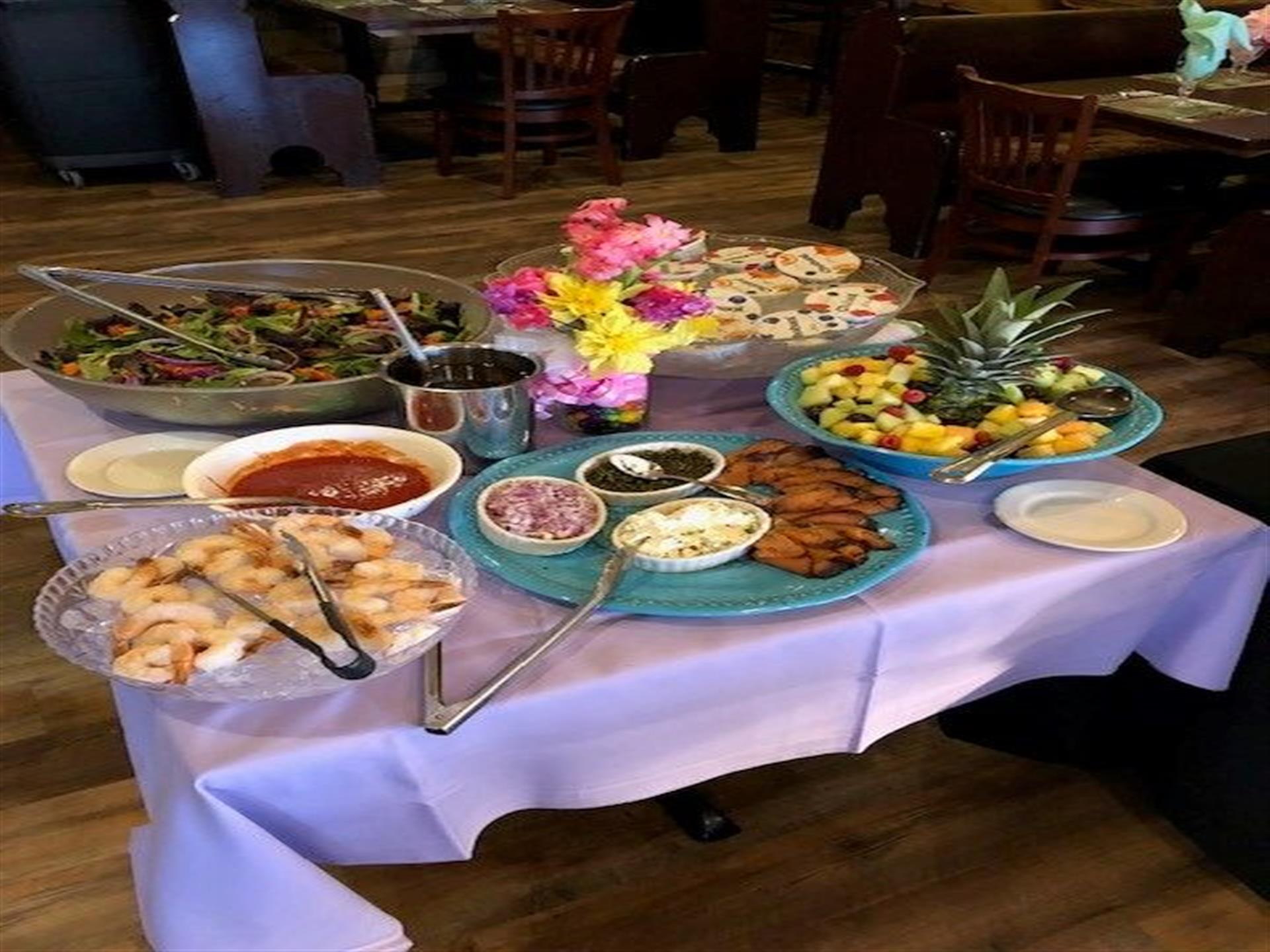 various platters of food displayed on a table with a purple tablecloth