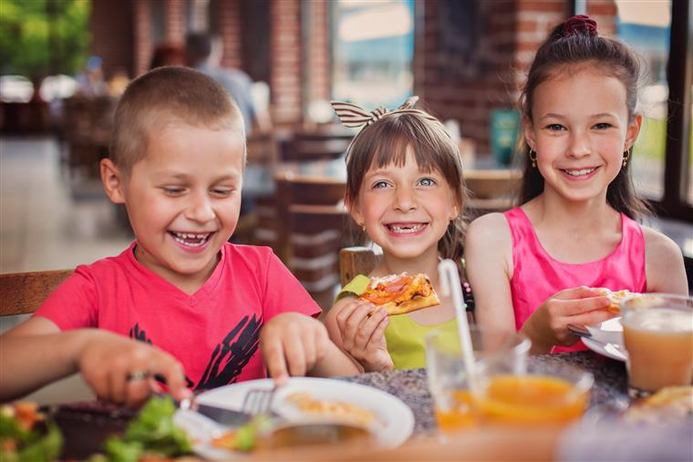 three kids sitting at a table eating