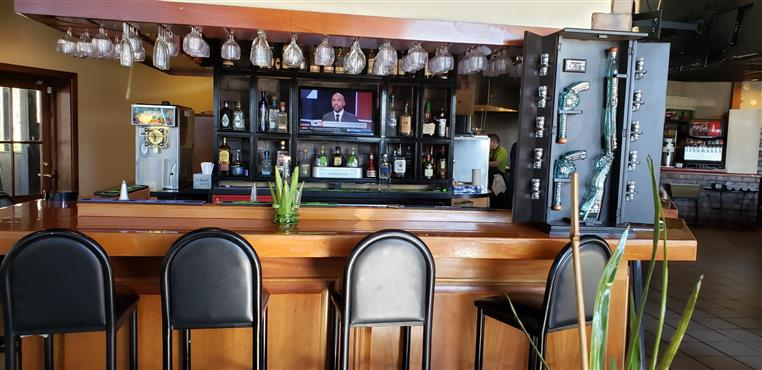 bar with bar stools and hanging wine glasses