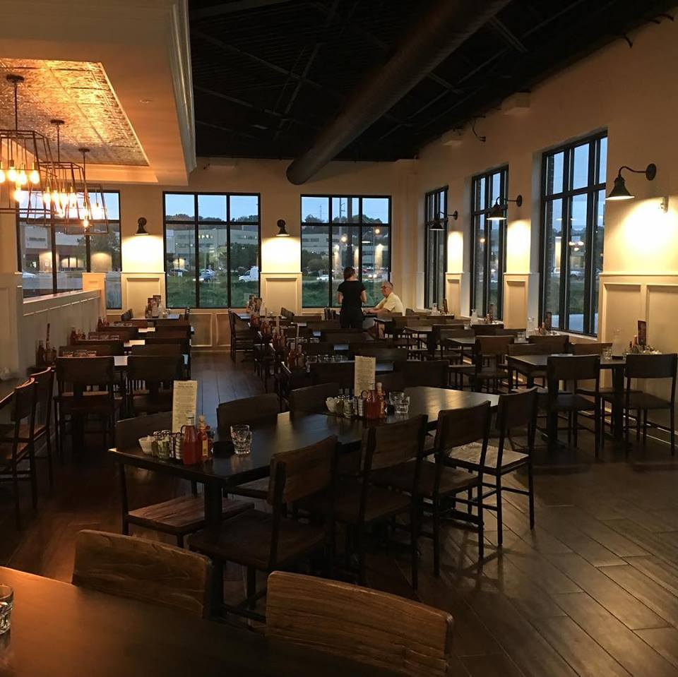 Interior dining area. White walls with tall windows. Dark wood floors and tables.