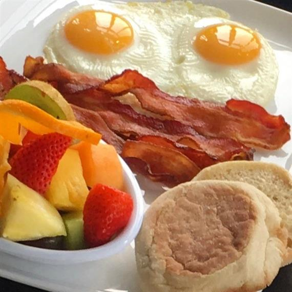 Two eggs sunny-side-up with bacon, English muffin and fruit salad on the side.