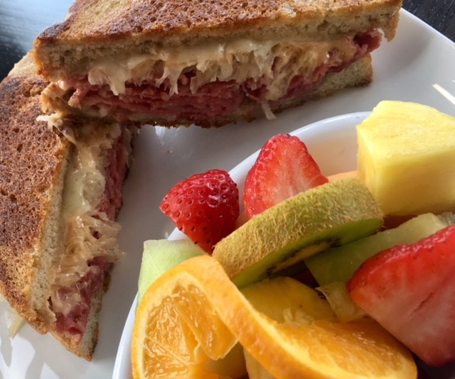 Reuben Sandwich with fruit salad on the side.