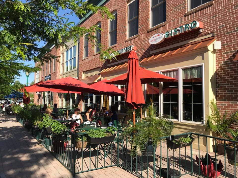 Exterior of Artful Gourmet showing patrons at outdoor seating under umbrellas