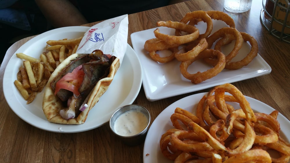 Greek Gyro in a pita with tomatoes, red onions and tzatziki sauce with curly fries on the side
