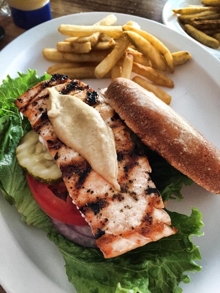 Salmon burger over pickles, tomatoes and lettuce with French fries on the side