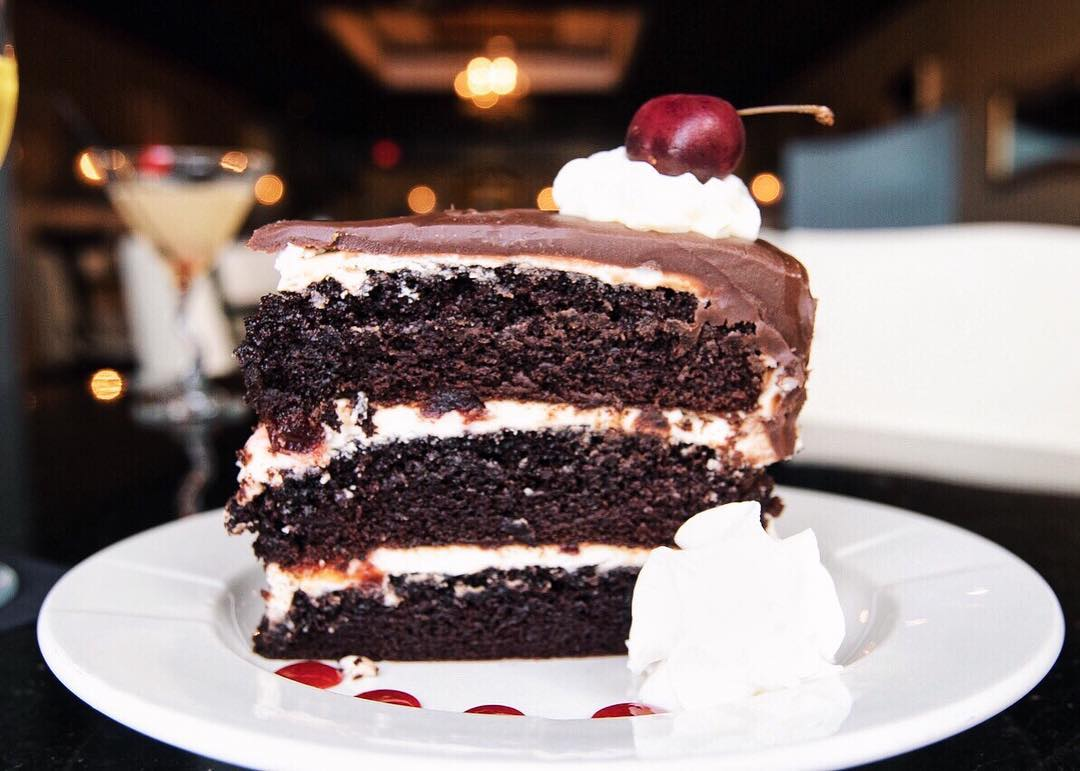 Triple layer chocolate cake with a cherry on top