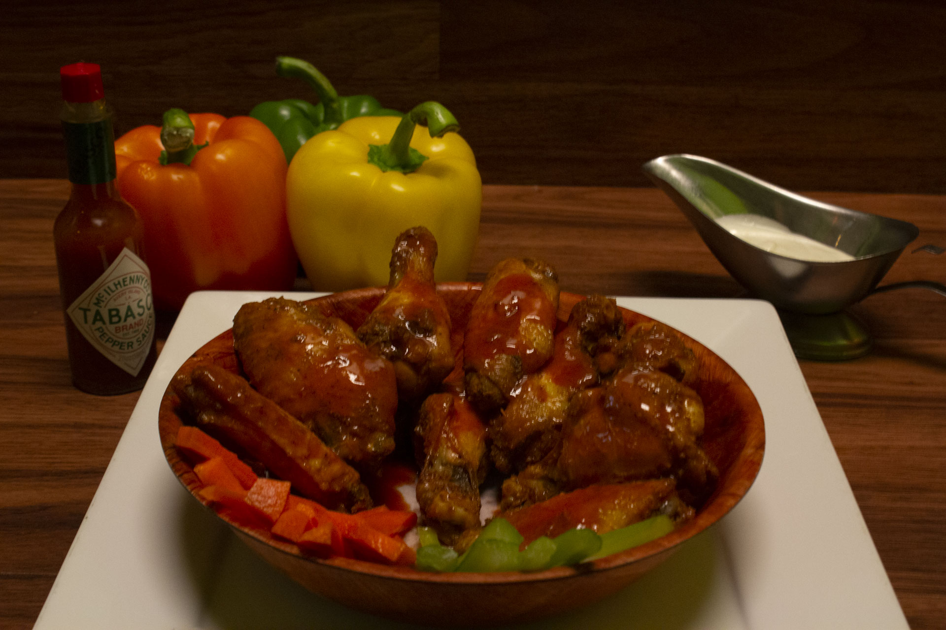 Chicken wings in a bowl with a bottle of Tabasco sauce, bell peppers, celery and side of bleu cheese.
