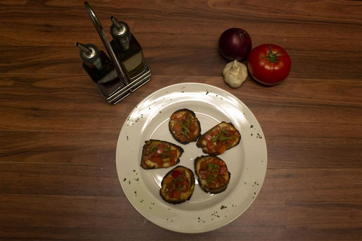 Top view of Bruschetta. Olive oil, garlic, onion and tomato on the side.