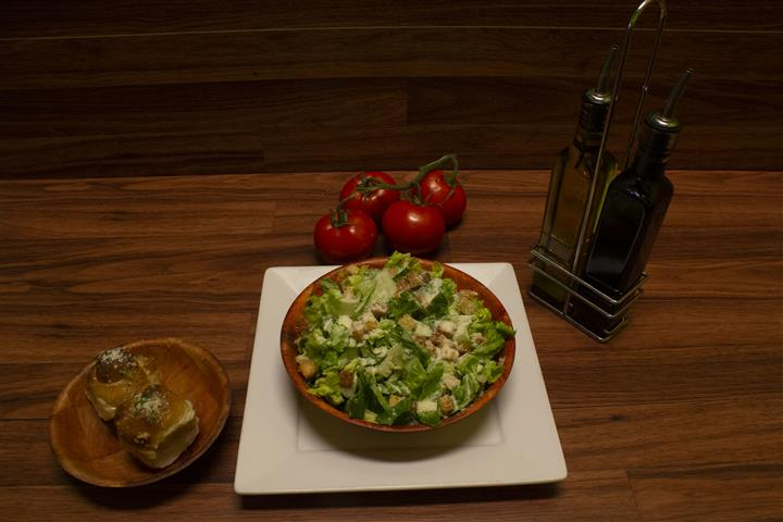 Top view of Caesar Salad with olive oil, garlic knots and tomatoes on the vine on the side.