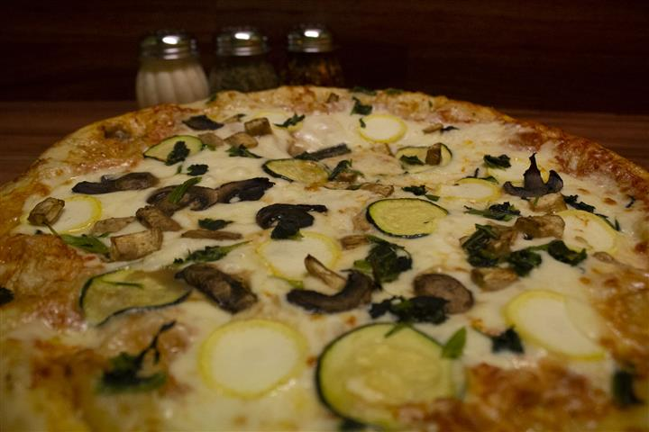 Close up View of Giardino Pizza. Pizza topped with tomato sauce, mozzarella, eggplant, spinach, yellow squash, zucchini & mushrooms.