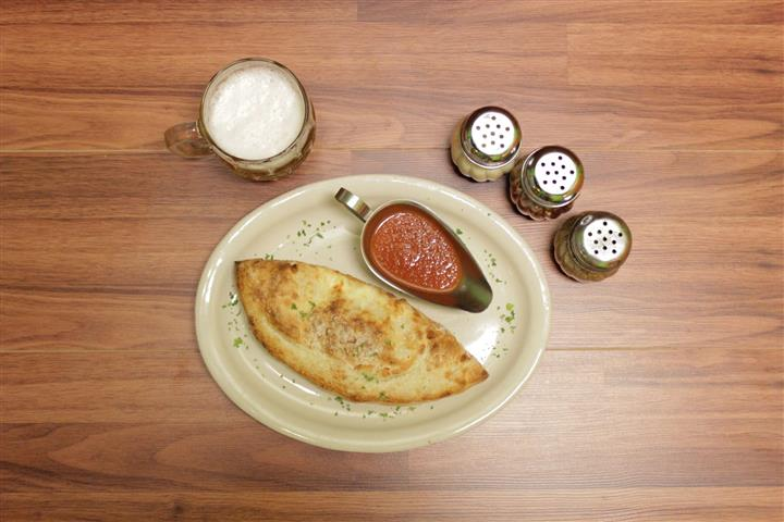 Top view of Calzone on a plate with a side of marinara sauce. Beer stein and spices on the side.