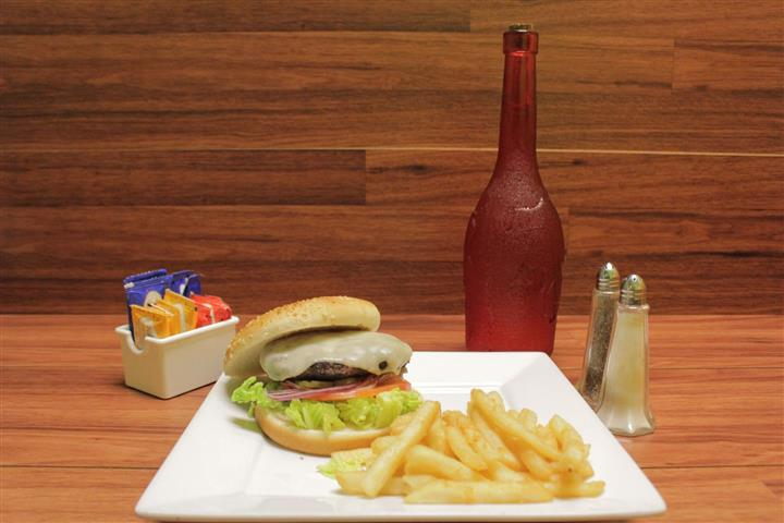 Cheeseburger topped with Swiss cheese with lettuce, tomato and onion. French fries, salt, pepper, sauces and unopened bottle of rosé on the side.