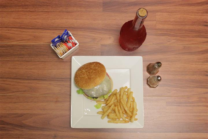 Top view of Cheeseburger topped with Swiss cheesewith lettuce, tomato and onion. French fries, salt, pepper, sauces and unopened bottle of rosé on the side.
