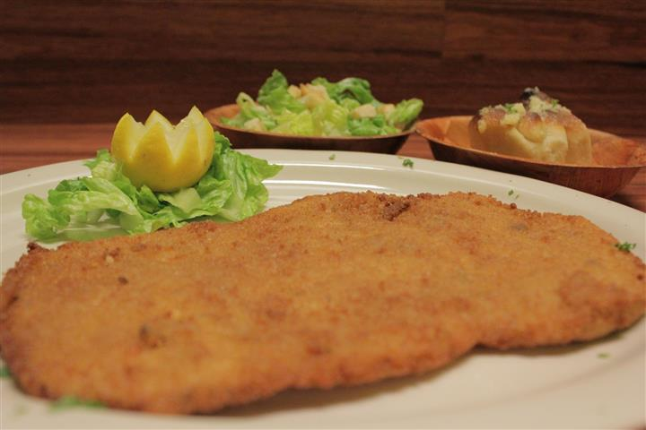 Chicken Milanese plate. Small Caesar salad and garlic knots on the side.