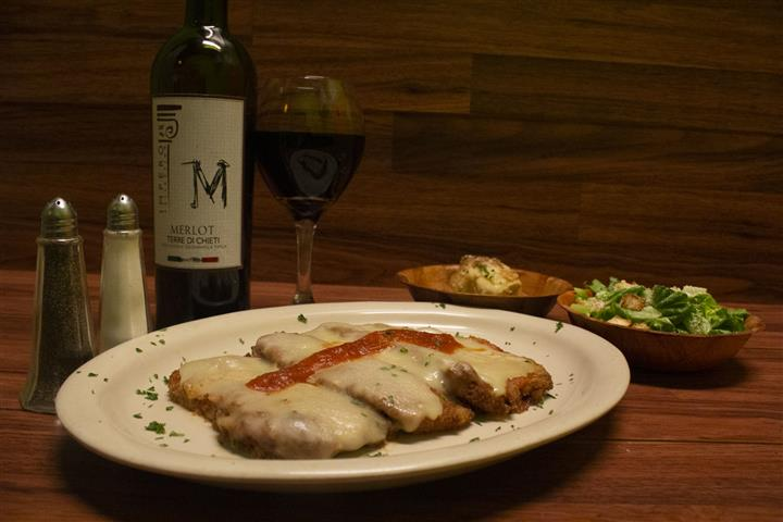 Chicken Parmigiana topped with melted mozzarella cheese and a touch of tomato sauce. Garlic knots and small Caesar salad on the side. Bottle of Terre Di Chieti Merlot poured into a wine glass.