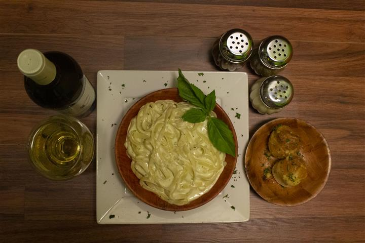 Top view of Fettuccini Alfredo in a bowl with basil leaves on top. Parmesan cheese, spices and garlic knots on the side. Bottle of Terre Di Chieti Chardonnay poured into a wine glass.