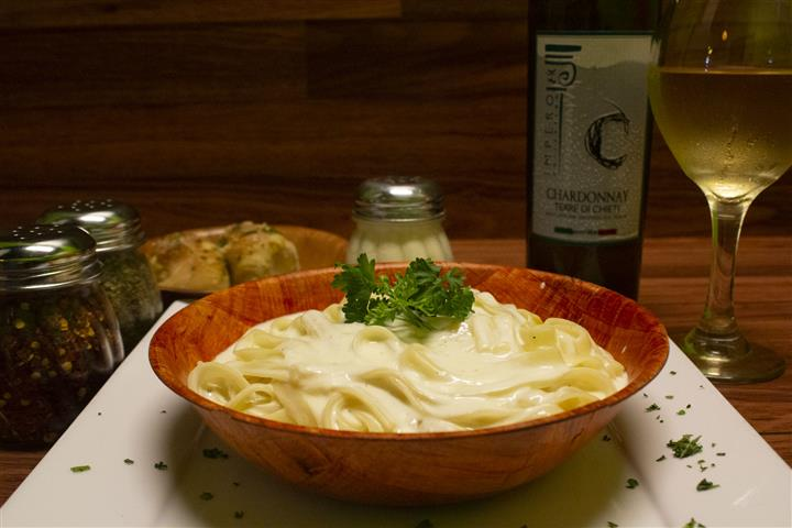 Fettuccini Alfredo in a bowl with basil leaves on top. Parmesan cheese, spices and garlic knots on the side. Bottle of Terre Di Chieti Chardonnay poured into a wine glass.