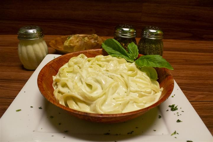 Fettuccini Alfredo in a bowl with basil leaves on top. Parmesan cheese, spices and garlic knots on the side.
