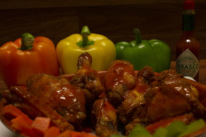 Close up of Chicken wings in a bowl with a bottle of Tabasco sauce and assorted bell peppers on the side.