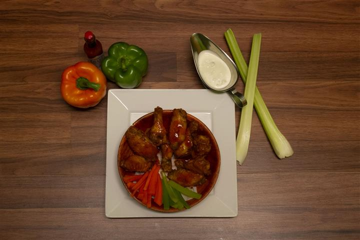 Top view of Chicken wings in a bowl with a bottle of Tabasco sauce, bell peppers, celery and side of bleu cheese.