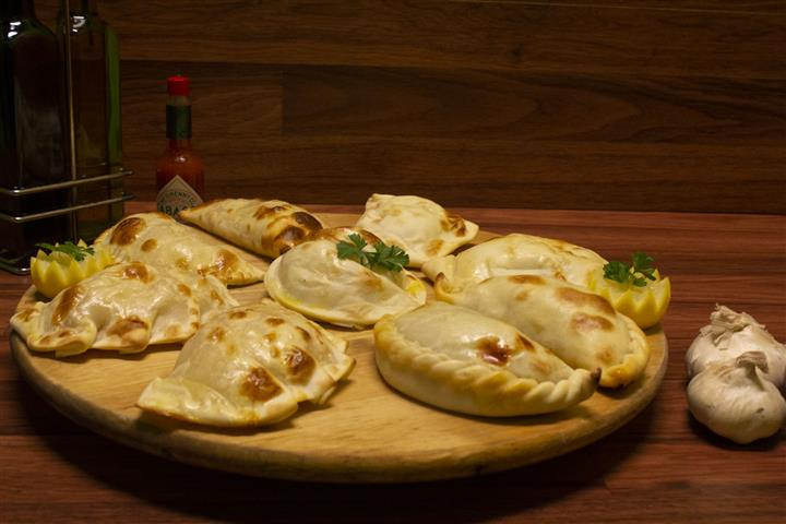 Assorted empanadas on a wood tray. Garlic, red onion, Tabasco Hot Sauce and olive oil on the side.