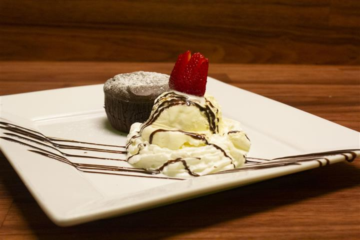 Side view of Chocolate Souffle on a square plate with a scoop of vanilla ice cream on the side. Ice cream topped with a strawberry and chocolate syrup drizzle.