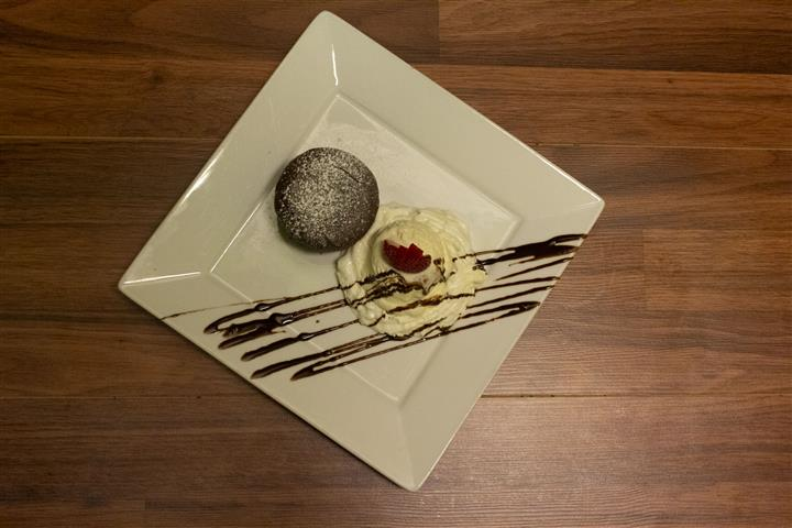 Top view of Chocolate Souffle on a square plate with a scoop of vanilla ice cream on the side. Ice cream topped with a strawberry and chocolate syrup drizzle.