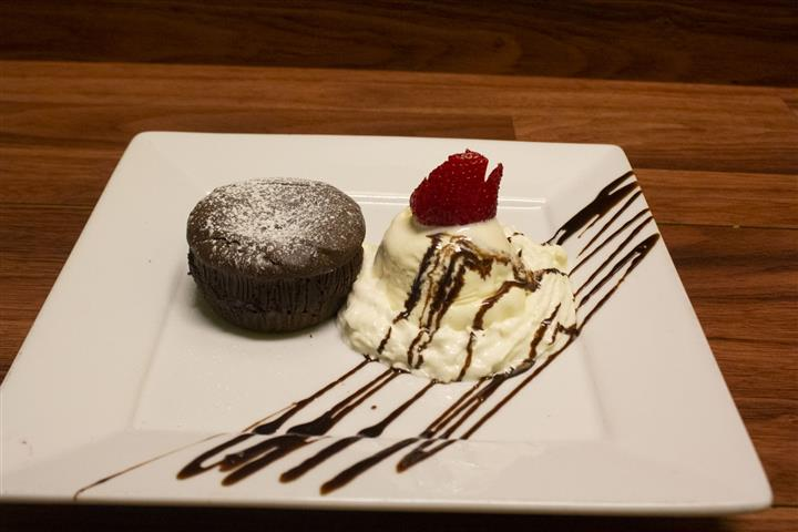 Chocolate Souffle on a square plate with a scoop of vanilla ice cream on the side. Ice cream topped with a strawberry and chocolate syrup drizzle.
