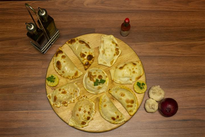 Top View of assorted empanadas on a wood tray. Garlic, red onion, Tabasco Hot Sauce and olive oil on the side.