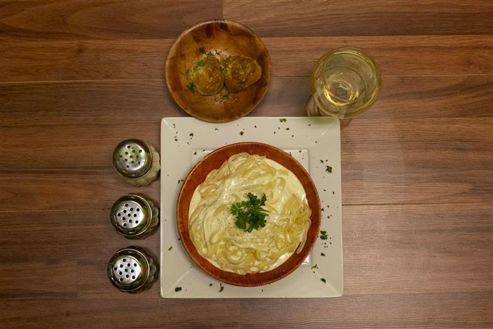 Top view of Fettuccini Alfredo in a bowl with basil leaves. Glass of white wine, spices and bowl of garlic knots on the side.