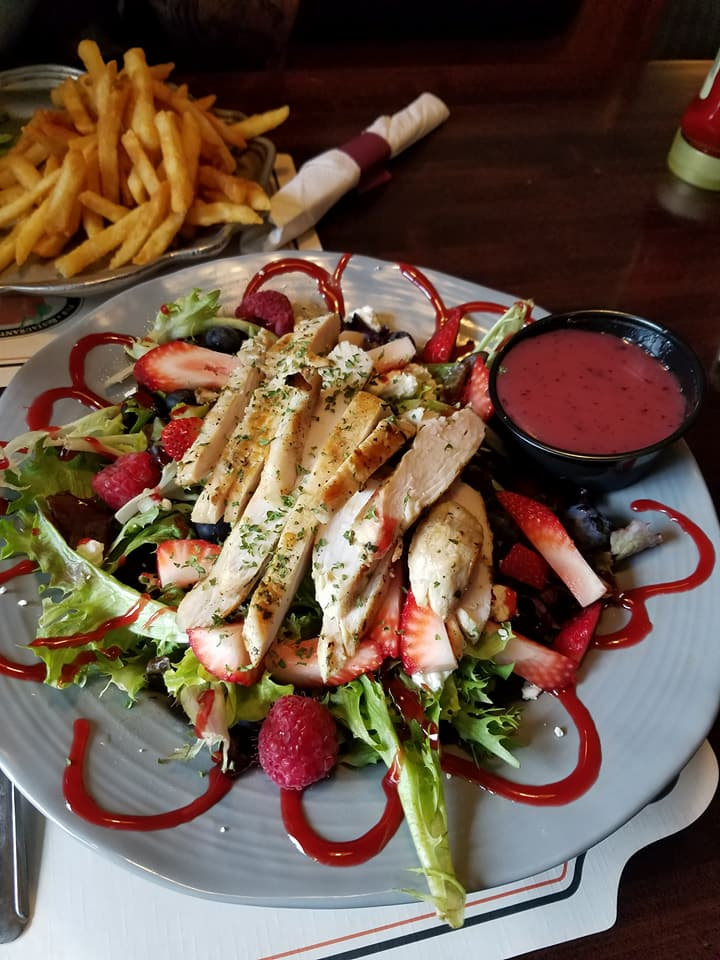 Grilled sliced chicken served over a bed of greens with raspberries and strawberries
