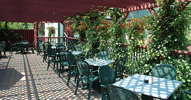 Outide patio area at Apple Valley restaurant. Green tables and chairs. Red pergola above on a sunny day.