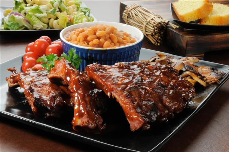 Barbecue ribs on a plate with baked beans on the side.