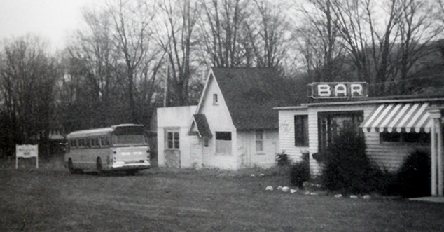 Vintage photo of the Bar in black and white. Bus parked in front.