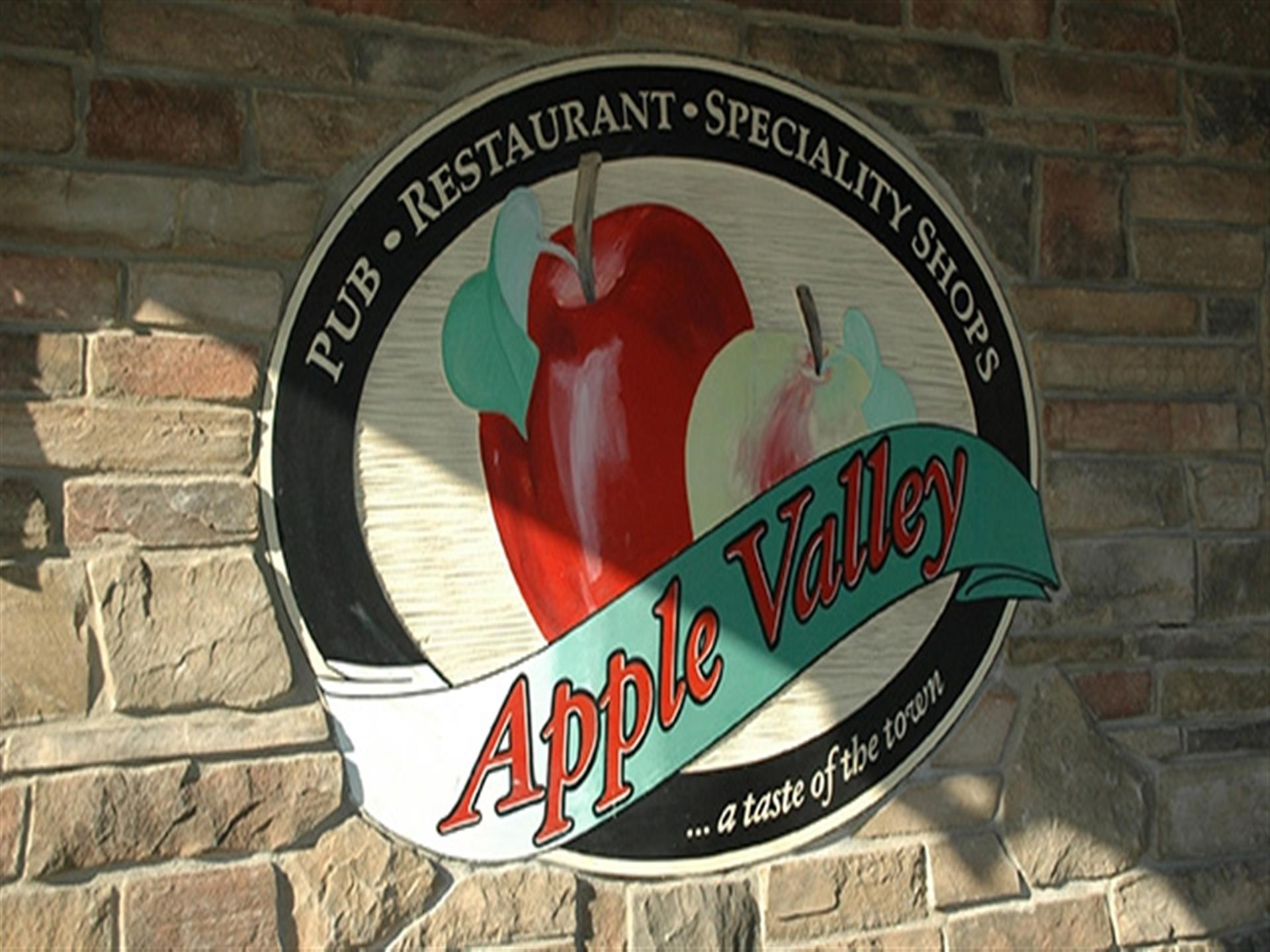 Apple Valley Sign on stone wall. Pub, Restaurant, Specialty shops. A taste of the town.