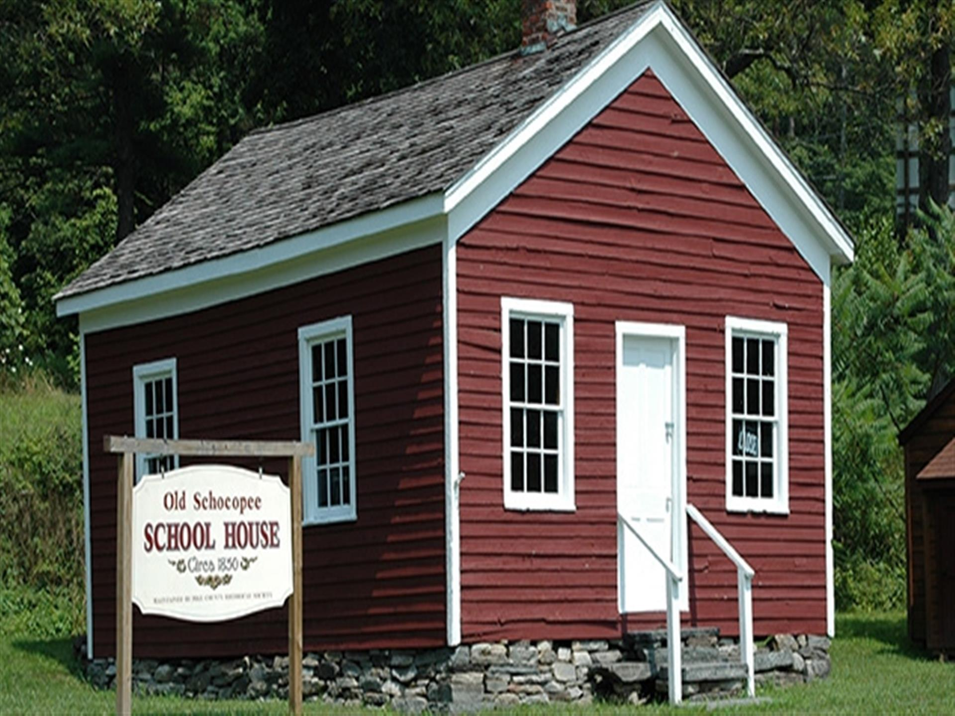 Old Schoepee School House. Since 1850. Red old school building with a sign out front.