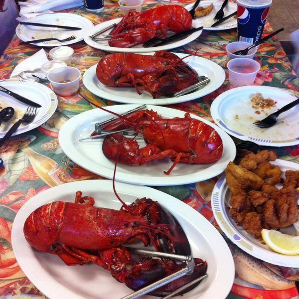 Plates of cooked full lobsters on a table with a plate of mixed fried seafood and lemon next to other empty plates with forks