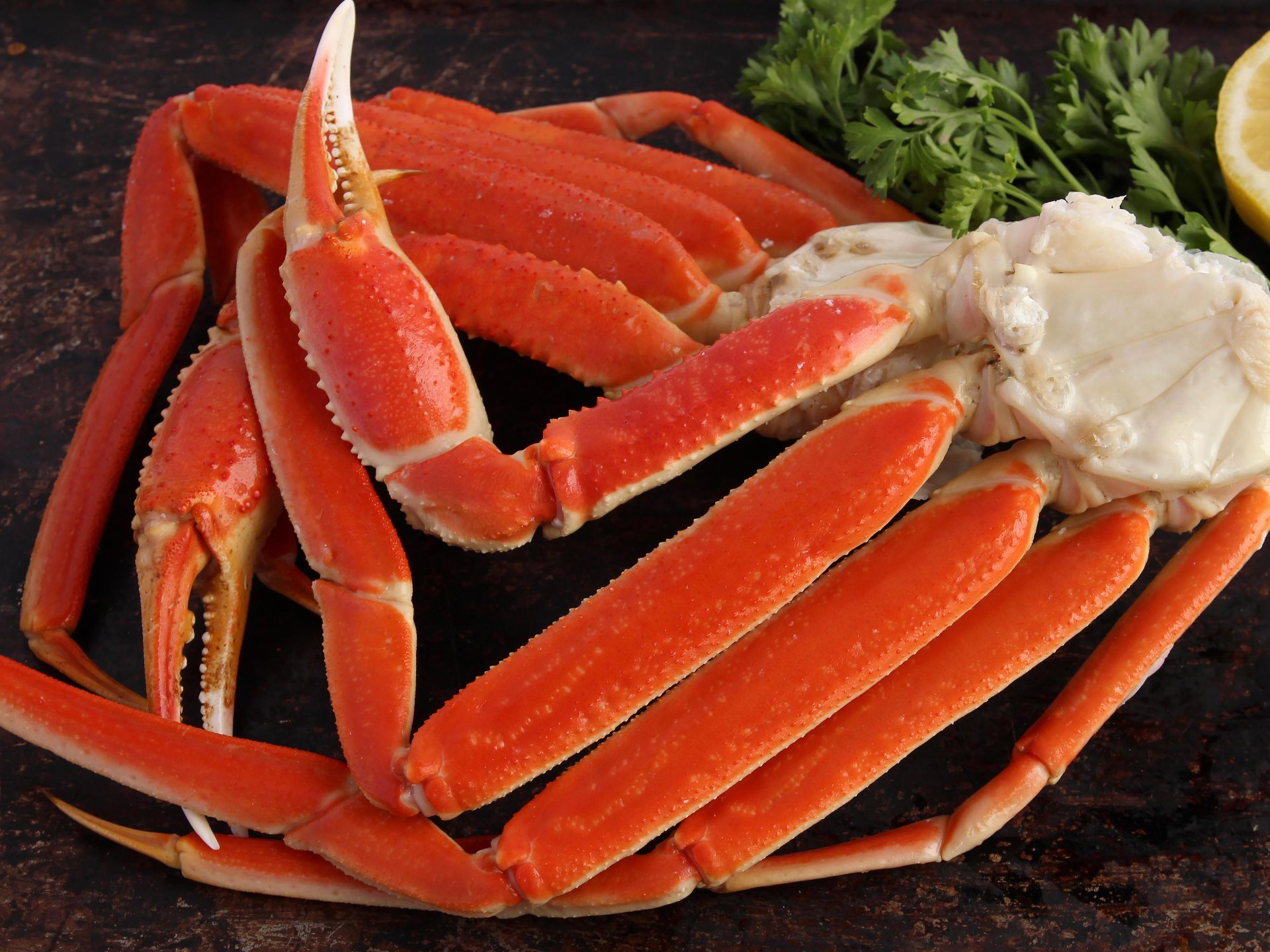 King crab legs on a dark wood background with parsley and lemon on the side