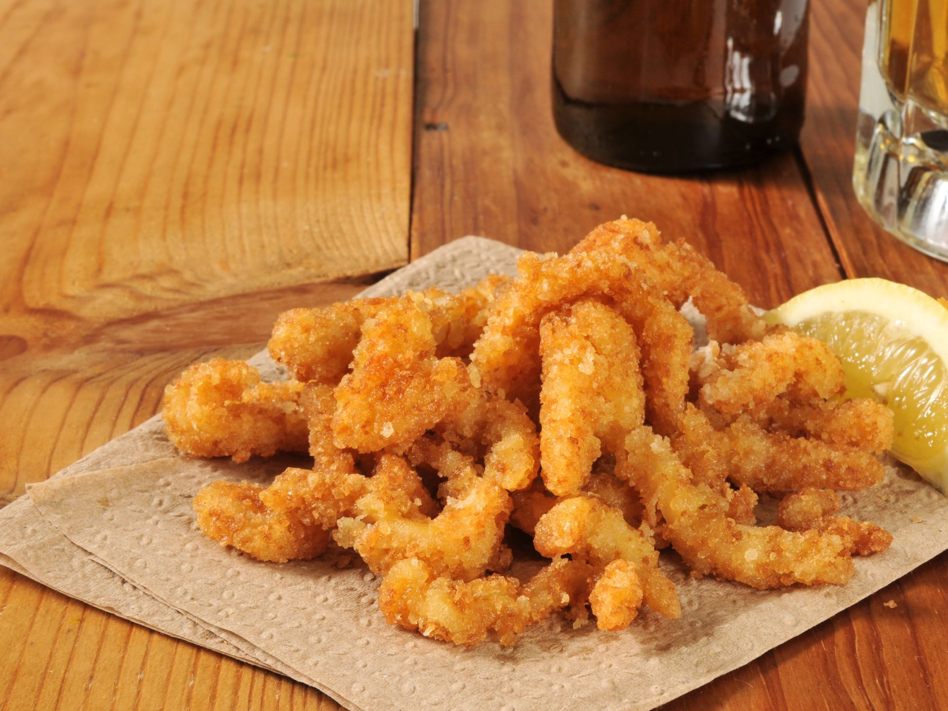 Fried clam strips on brown paper with a lemon slice and two glass bottles in the background on a wooden table