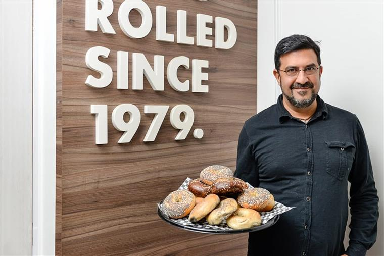 Rolled Since 1979. Ben holding a tray of assorted bagels.