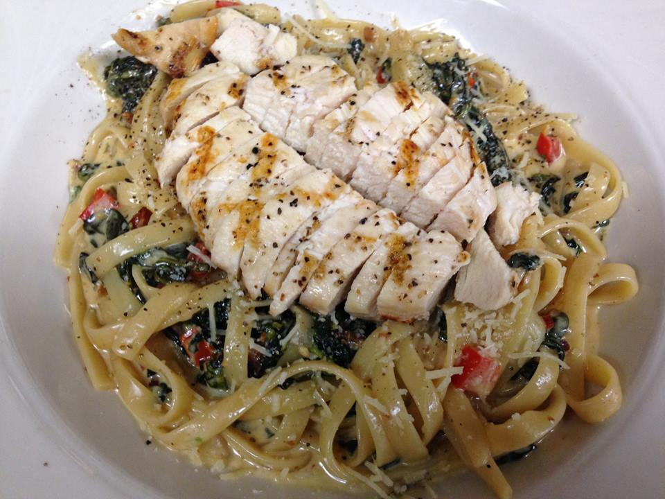 Grilled chicken over spaghetti with olive oil, cheese, spinach and tomatoes